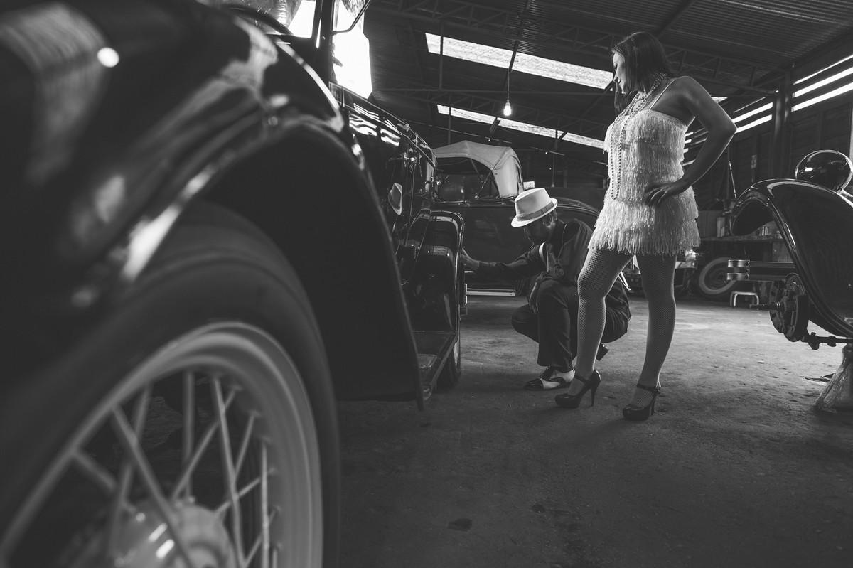 Ensaio de casal no estilo máfia feito pelo fotógrafo de casamentos de Brasília-DF. Oficina de carros antigos.