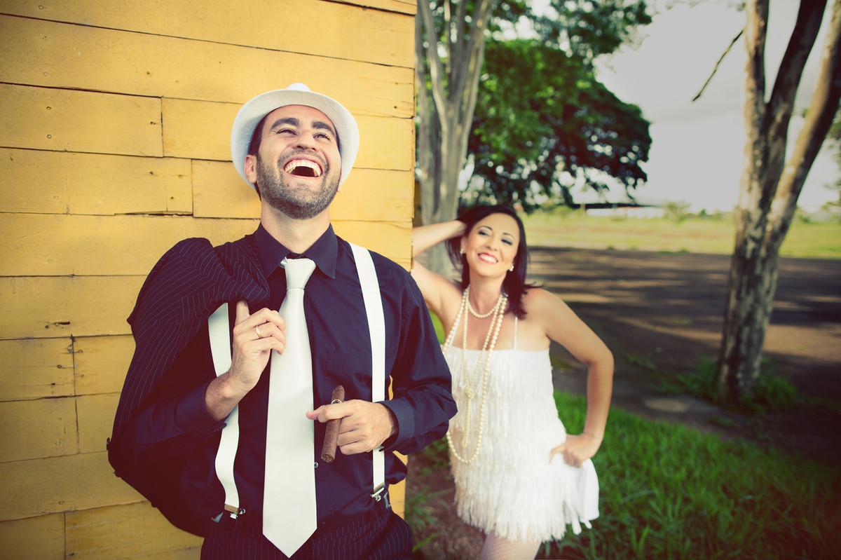 Ensaio de casal no estilo máfia feito pelo fotógrafo de casamentos de Brasília-DF. Casal rindo.