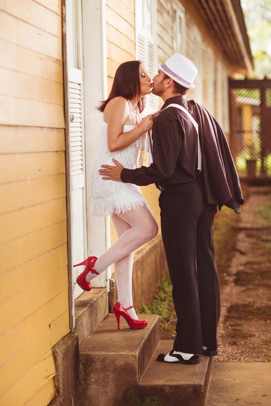 Ensaio de casal no estilo máfia feito pelo fotógrafo de casamentos de Brasília-DF. Casal beijando.