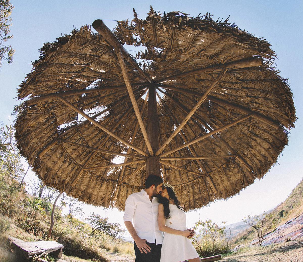 Casal baijando debaixo da sombrinha. Fotografado pelo fotografo de casamento Rafael Ohana em Brasilia-DF