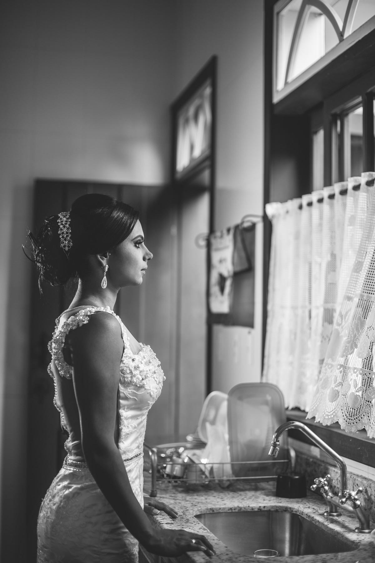 Noiva olhando pela janela da cozinha foto feita pelo fotógrafo Rafael Ohana em Paracatu-M