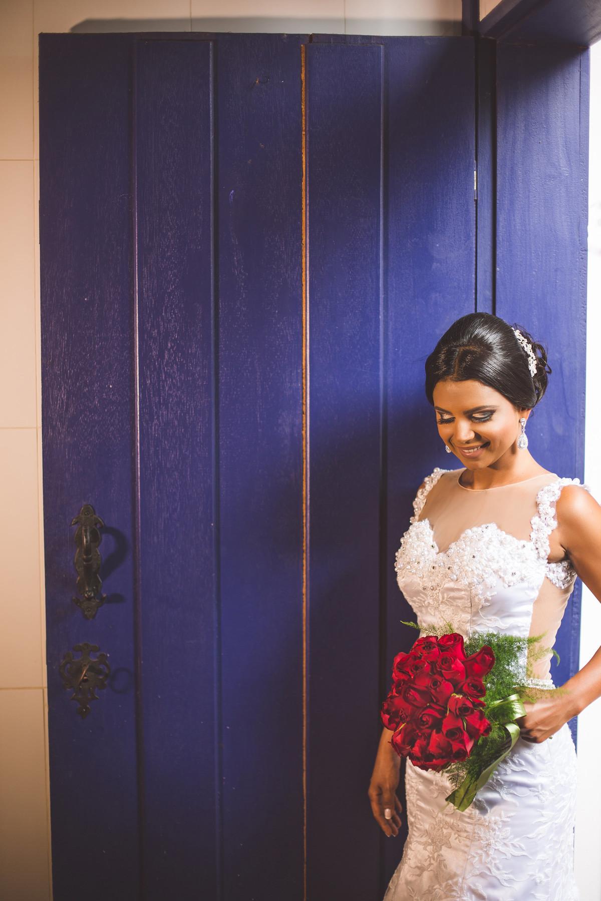 Noiva posando em porta azul foto feita pelo fotógrafo Rafael Ohana em Paracatu-M