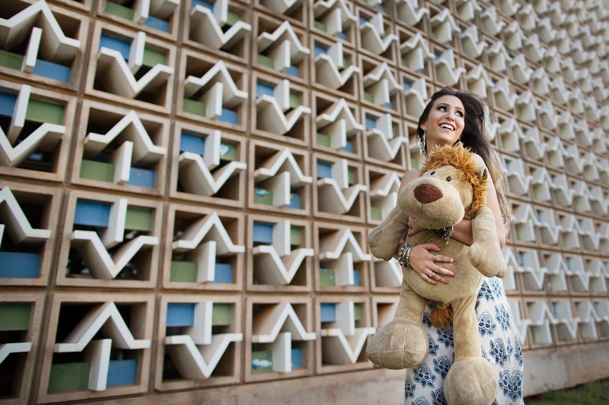 Ensaio de 15 anos com menina correndo com urso de pelúcia foto feita pelo fotógrafo Rafael Ohana em Brasília-DF