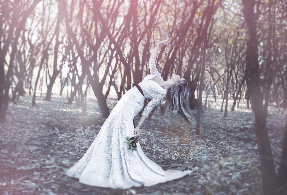 Noiva contorcendo o corpo segurando flores mortas em ensaio Trash the Dress feito pelo fotografo de casamentos Rafael Ohana em Brasilia-DF