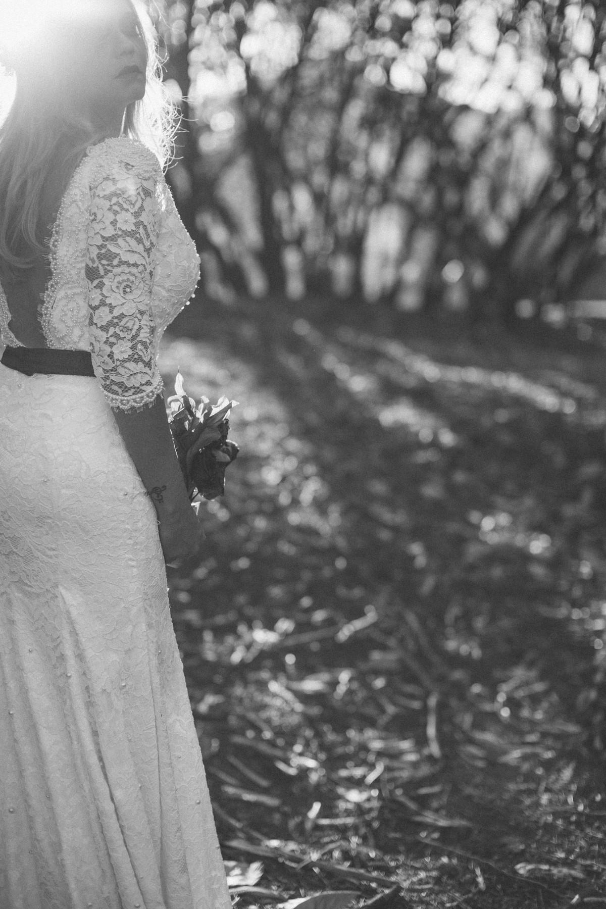 Noiva posando contra a luz segurando flores mortas feito pelo fotografo de casamentos Rafael Ohana em Brasilia-DF