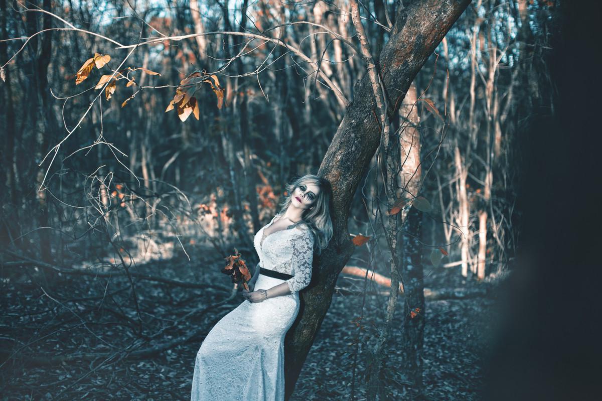 Noiva encostada em árvore em ensaio trash the dress de halloween feito pelo fotografo de casamento Rafael Ohana em Brasilia-DF