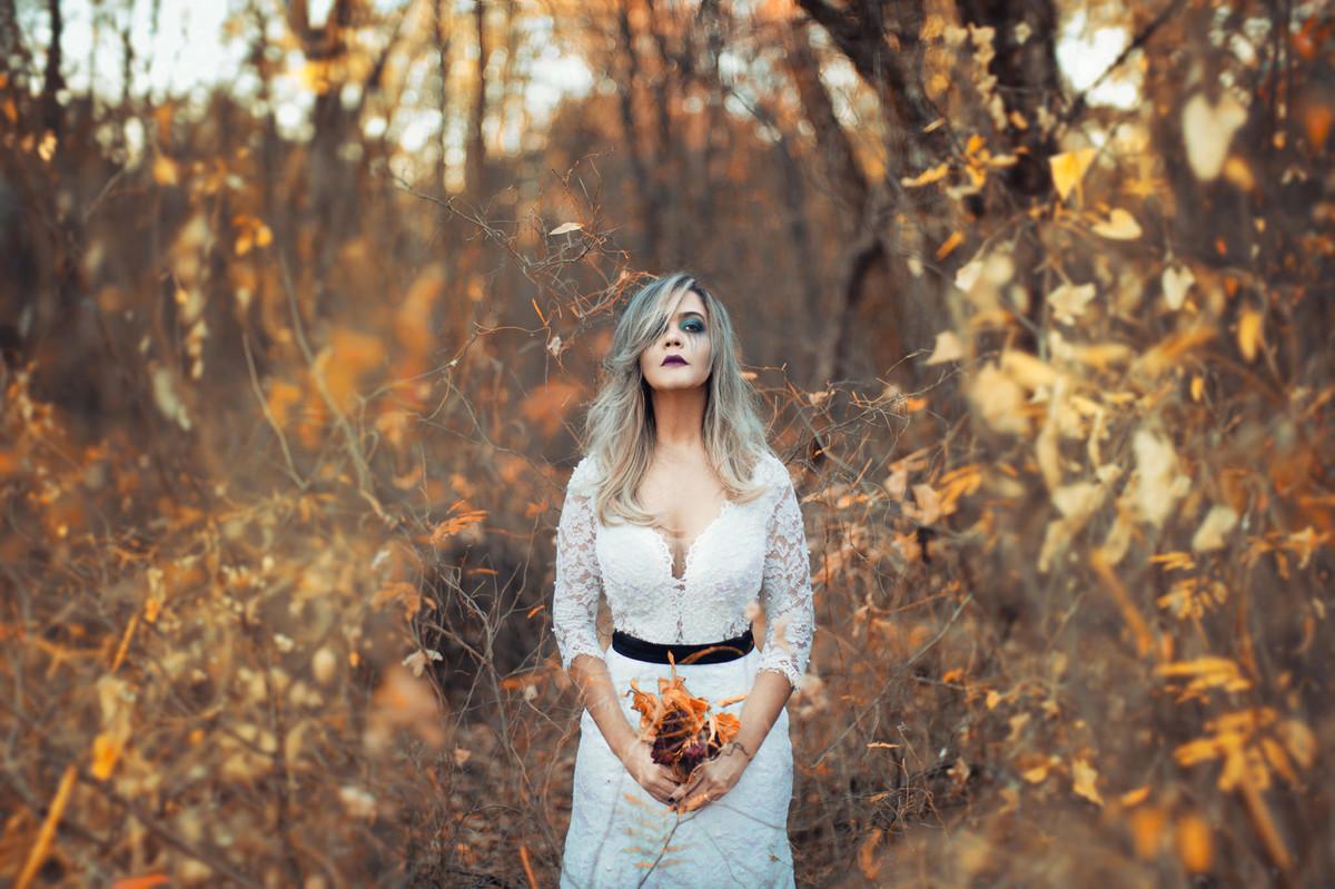 Noiva loira sozinha segurando flores mortas em ensaio Trash the Dress feito pelo fotógrafo de casamento Rafael Ohana em Brasilia-DF