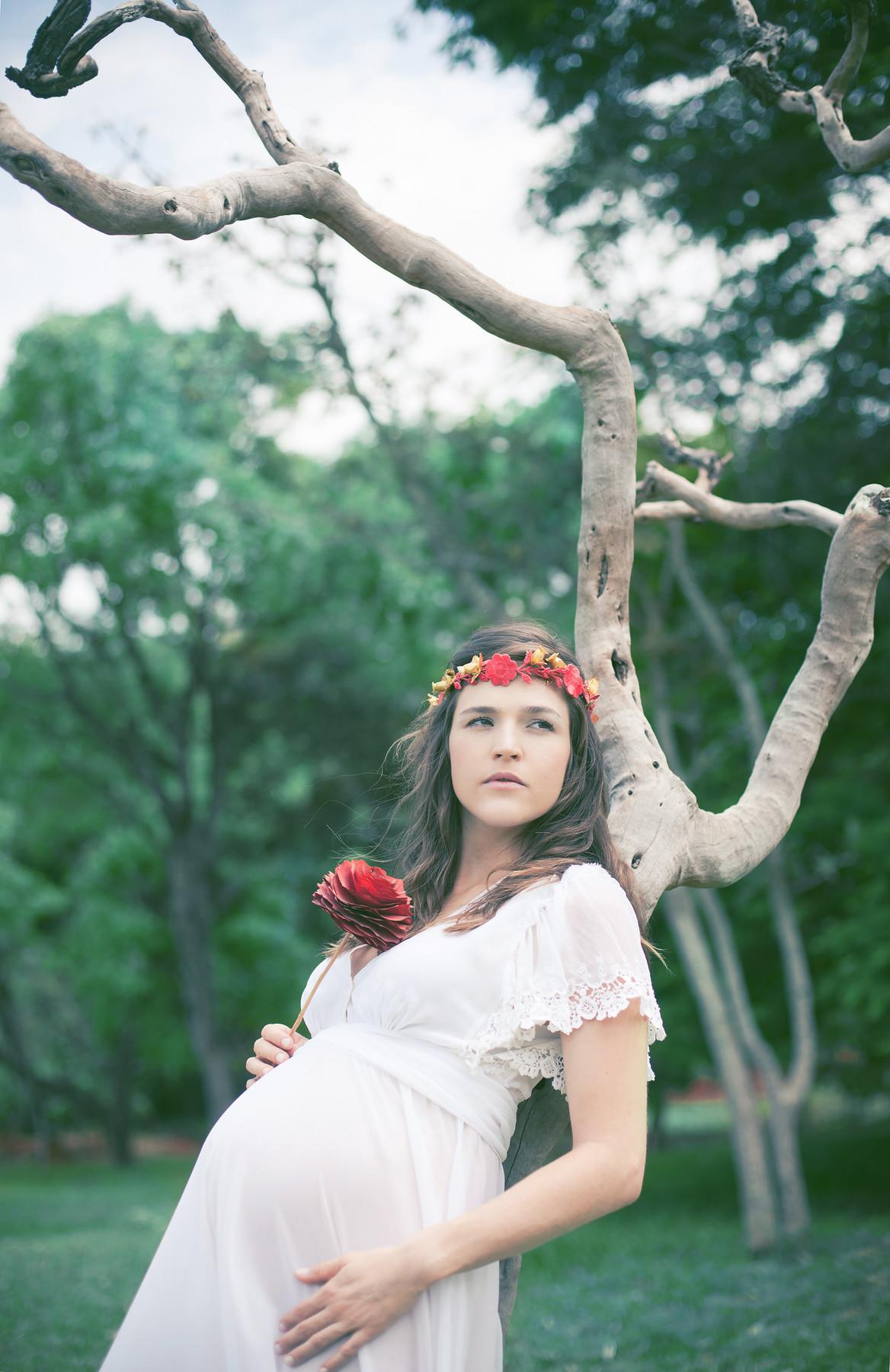 Gestante posando e olhando para o horizonte segurando flores vermelhas encostada em uma árvore. Fotografada pelo fotógrafo de gestantes Rafael Ohana em Brasília-DF