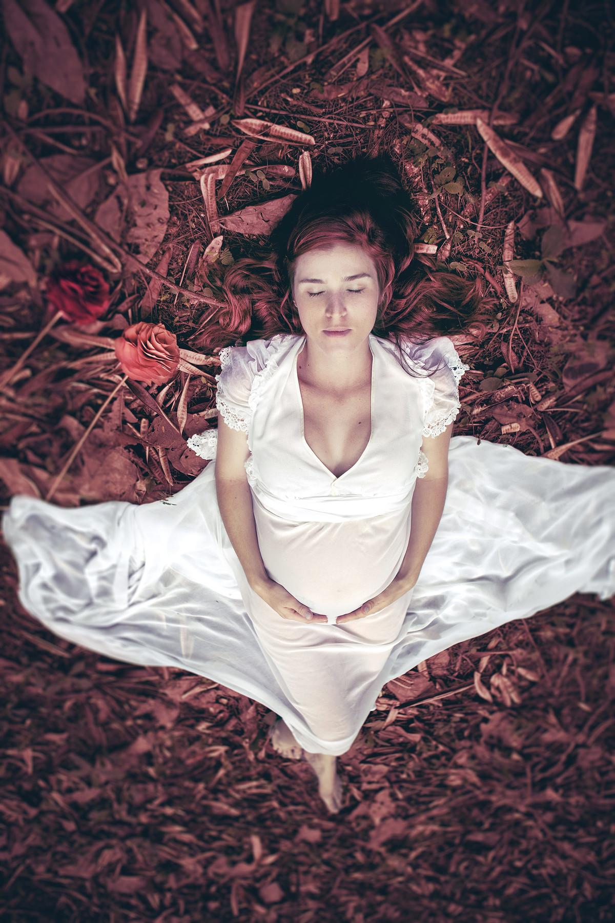 Grávida deitada no chão de olhos fechados usando um vestido branco.