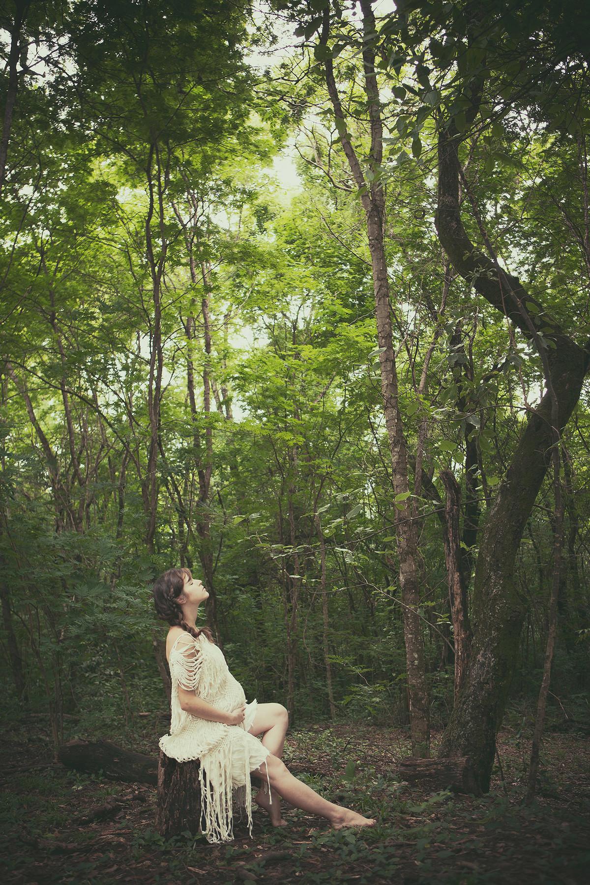 Grávida posando no estilo índia americana contemplando uma floresta em Brasília-DF