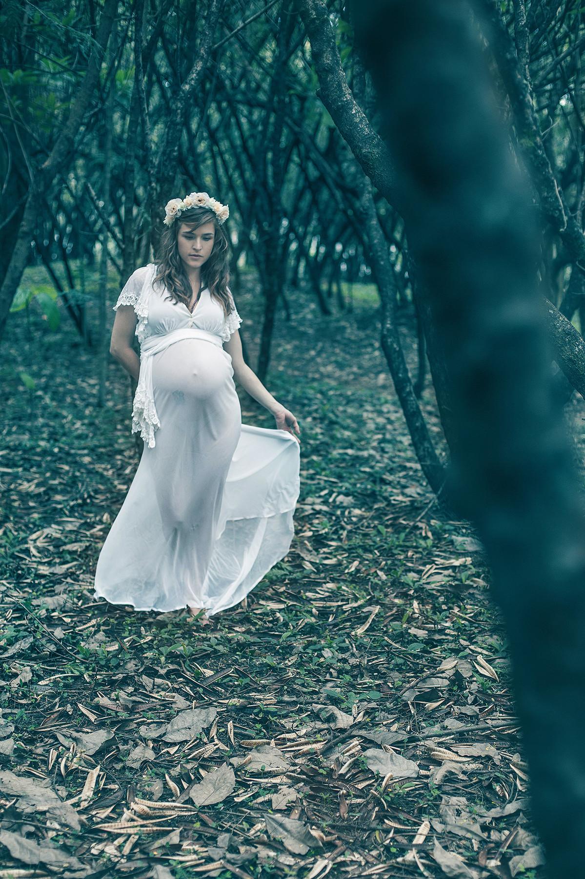 Gestante andando pela floresta com vestido branco