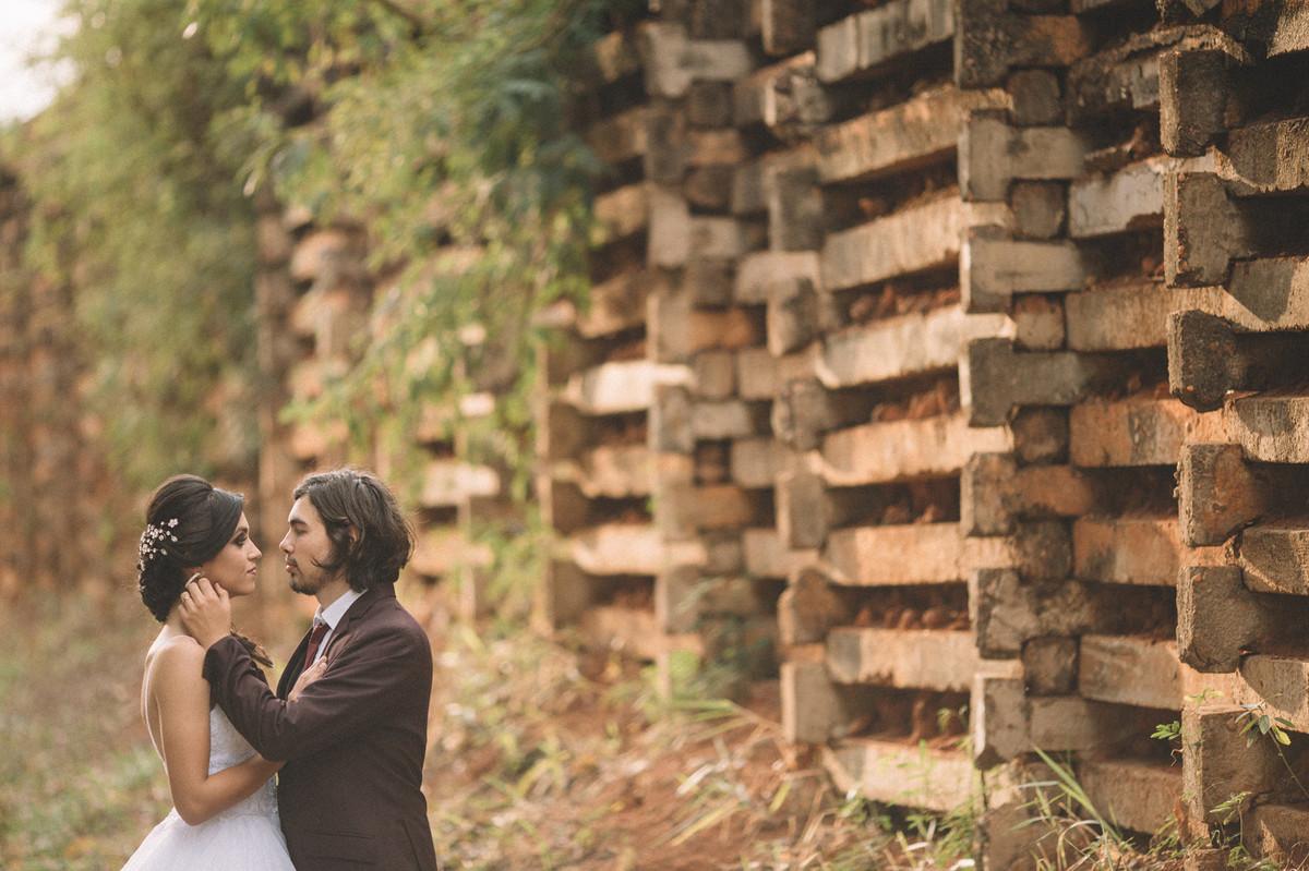 Casal de noivos se olhando perto de um muro alto. Fotografado pelo fotógrafo de casamento Rafael Ohana em Brasília-DF