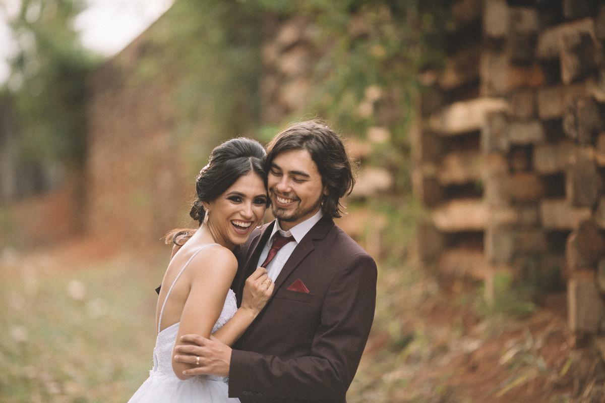 Casal abraçado rindo e se divertindo perto de um muro cheio de folhas. Fotografado pelo fotógrafo de casamento Rafael Ohana em Brasília-DF