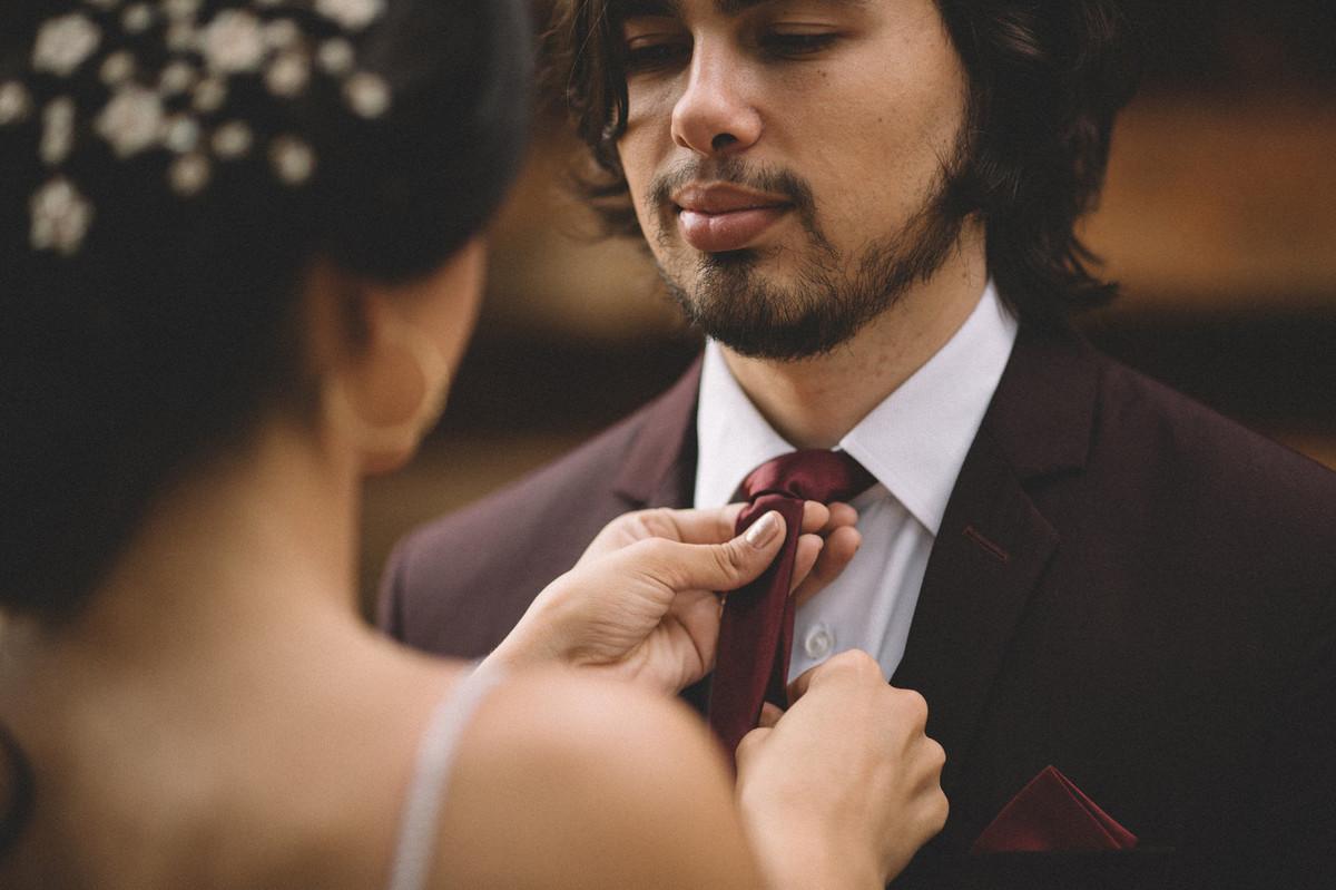Noiva arrumando a gravata do noivo que olha pra ela. Fotografado pelo fotógrafo de casamento Rafael Ohana em Brasília-DF