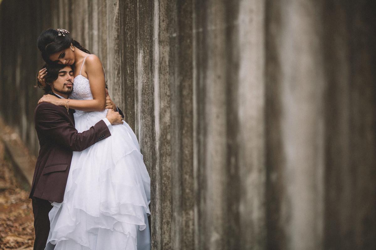 Noivos abraçados de olhos fechados ao lado de um grande muro de concreto. Fotografado pelo fotógrafo de casamento Rafael Ohana em Brasília-DF