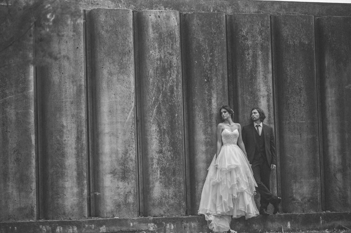 Noivos encostados em um grande muro de concreto. Fotografado pelo fotógrafo de casamento Rafael Ohana em Brasília-DF