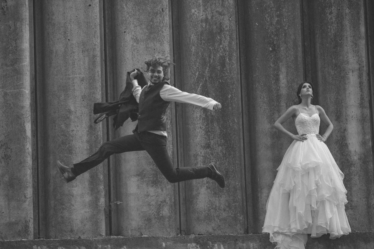 Noivo pulando segurando paletó enquanto noiva olha para cima. Fotografado pelo fotógrafo de casamento Rafael Ohana em Brasília-DF