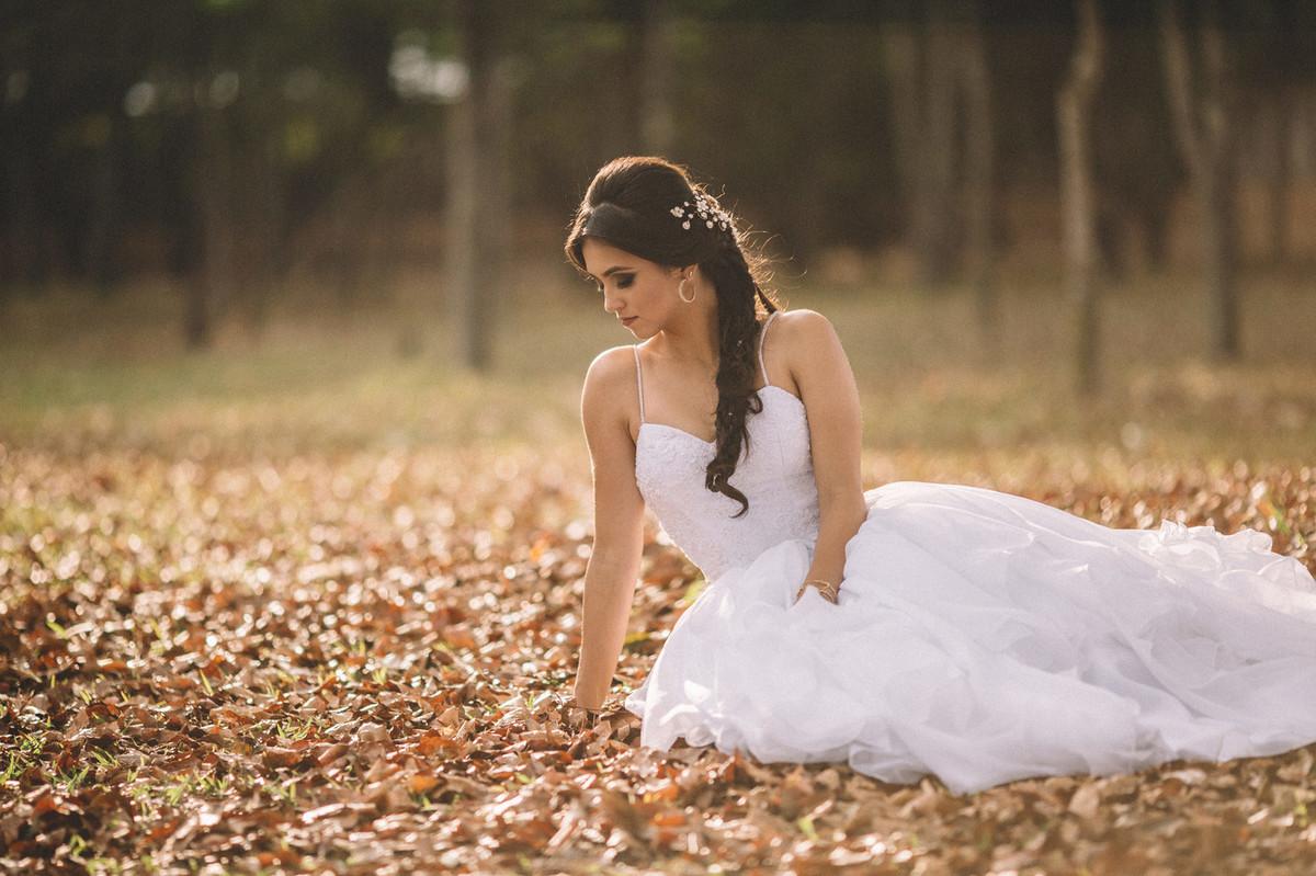 Noiva sozinha sentada no chão cheio de folhas. Fotografado pelo fotógrafo de casamento Rafael Ohana em Brasília-DF