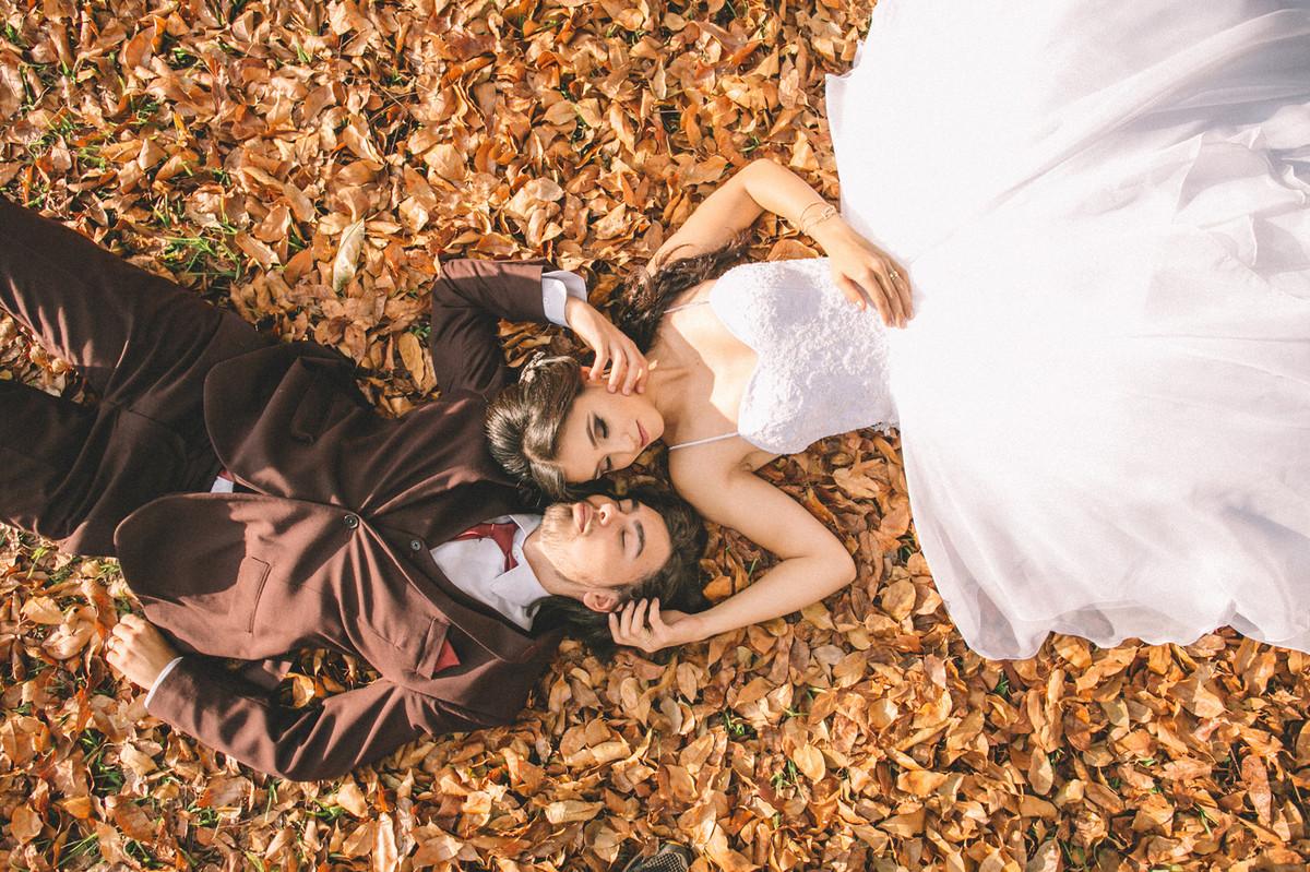 Noivos deitados no chão cheio de folhas. Fotografado pelo fotógrafo de casamento Rafael Ohana em Brasília-DF