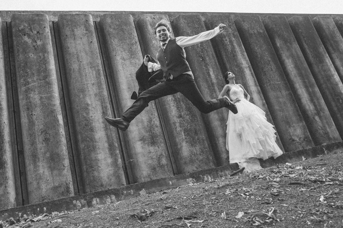 Noivo pulando alto enquanto noiva olha pra cima. Fotografado pelo fotógrafo de casamento Rafael Ohana em Brasília-DF