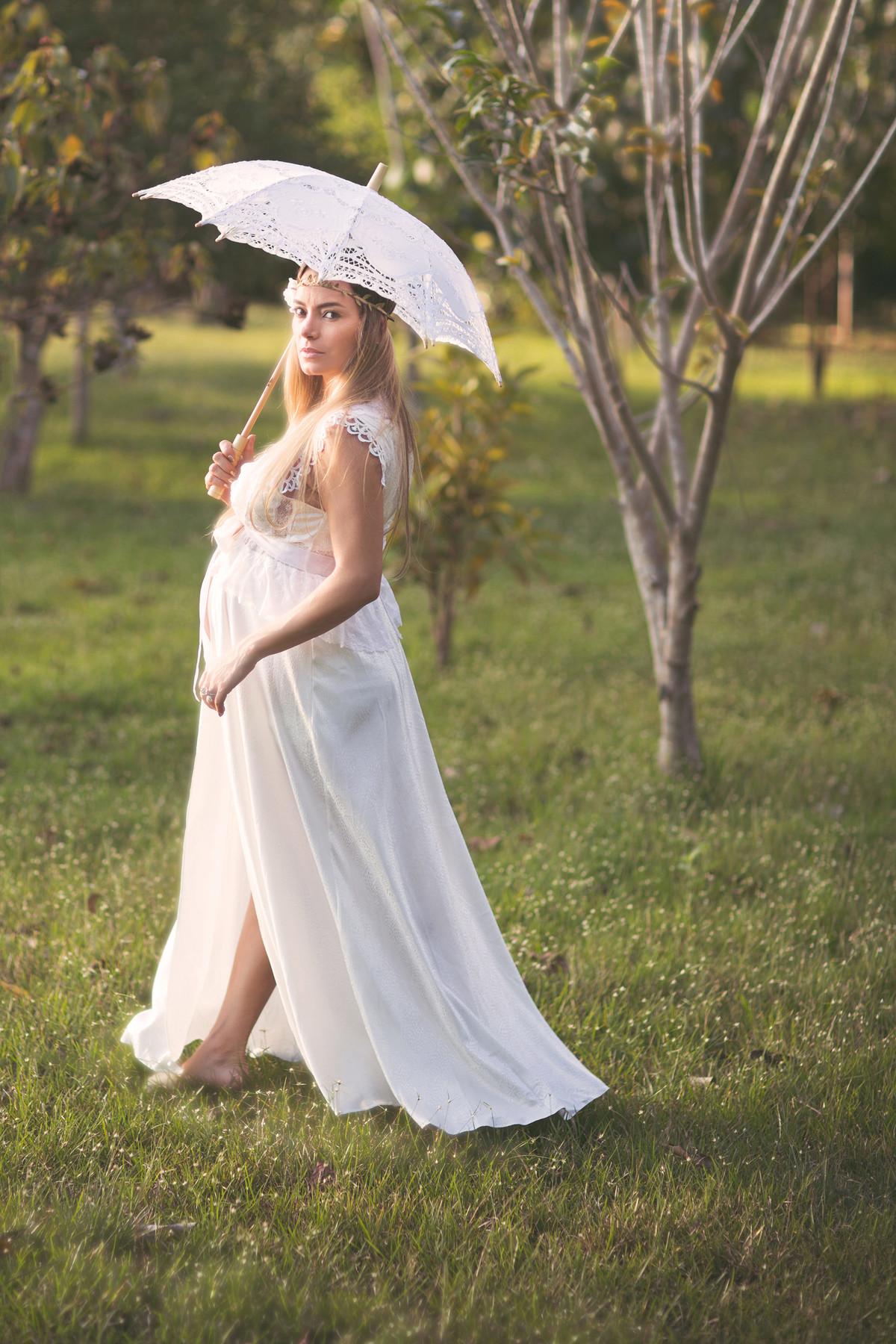 Grávida passeando pelo campo de vestido branco e sombrinha branca de renda. Fotografado pelo fotógrafo de gestantes Rafael Ohana em Manaus-AM