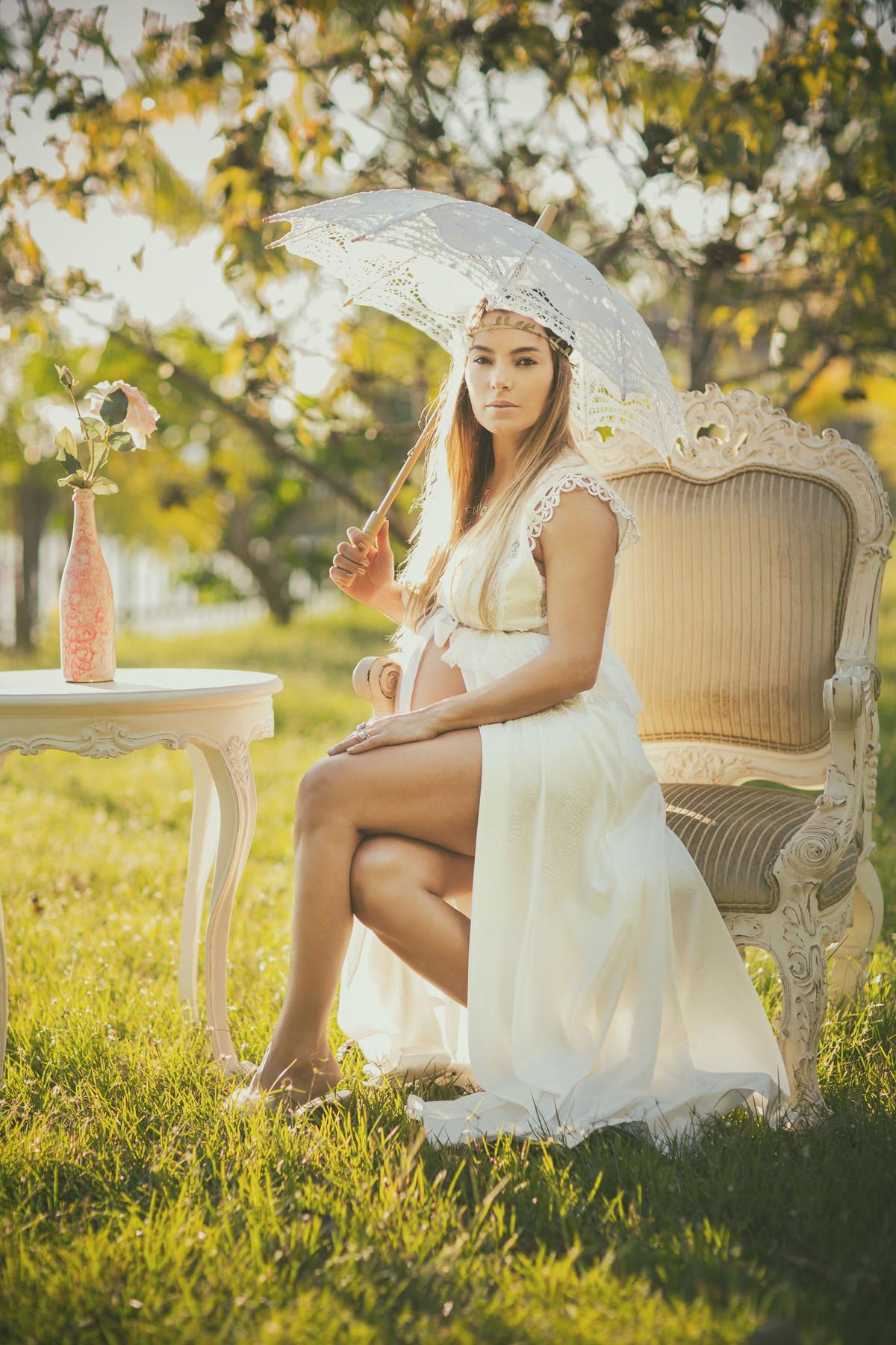 Grávida sentada em cadeira clássica usando um vestido branco e sombrinha de renda branca. Fotografado pelo fotógrafo de gestantes Rafael Ohana em Manaus-AM