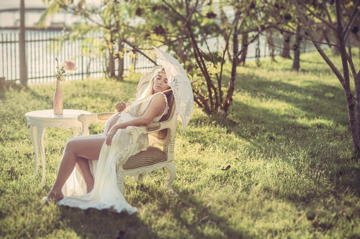 Grávida loira sentada em cadeira clássica vestindo um vestido branco segurando uma sombrinha de renda branca. Fotografado pelo fotógrafo de gestantes Rafael Ohana em Manaus-AM
