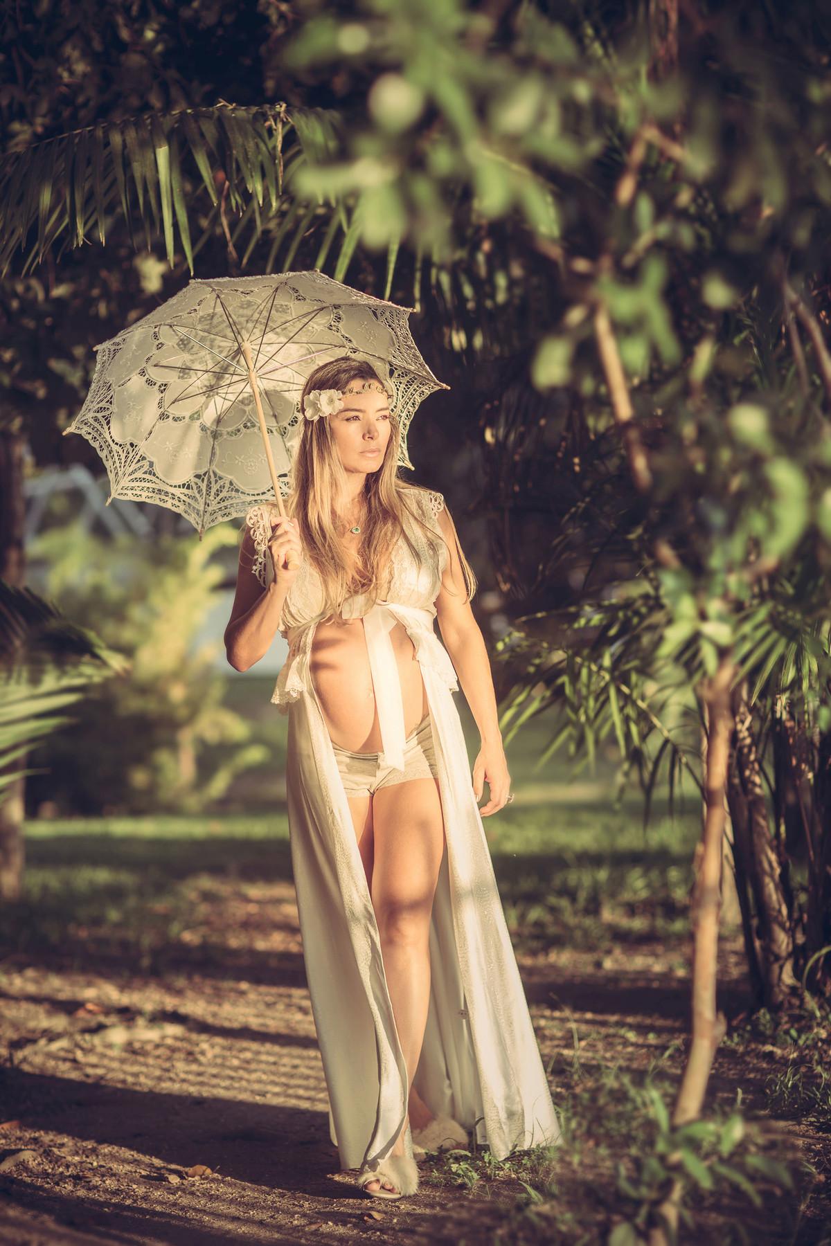 Grávida passeando pela floresta usando vestido branco e uma sombrinha branca de renda. Fotografado pelo fotógrafo de gestantes Rafael Ohana em Manaus-AM