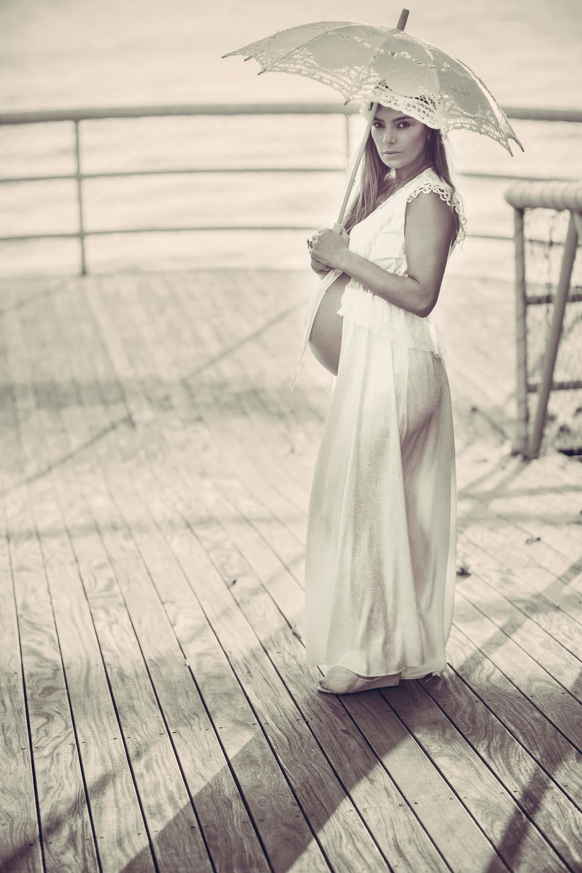 Grávida usando vestido branco e segurando sombrinha branca. Fotografado pelo fotógrafo de gestantes Rafael Ohana em Manaus-AM