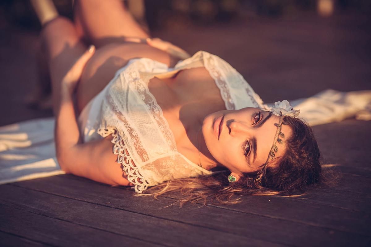 Grávida deitada com luz amarelada em pose sensual. Fotografado pelo fotógrafo de gestantes Rafael Ohana em Manaus-AM