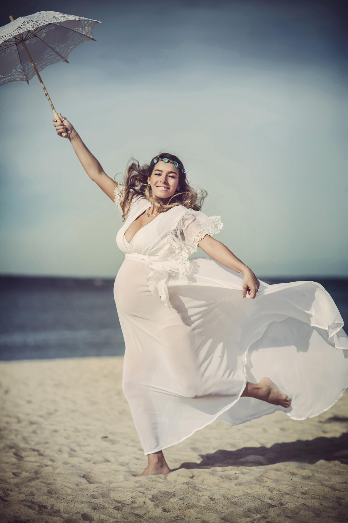Grávida pulando segurando uma sombrinha branca de renda. Fotografado pelo fotógrafo de gestantes Rafael Ohana em Manaus-AM