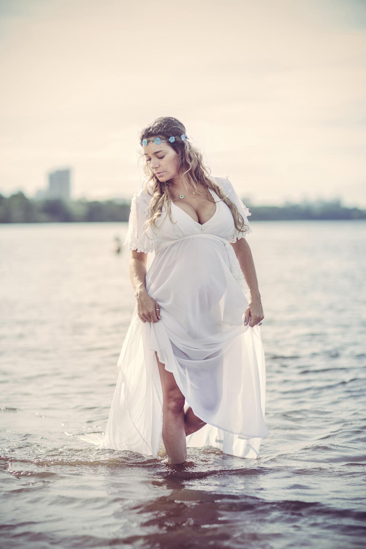 Grávida passeando na agua da praia do rio negro com seu vestido branco e guirlanda de flores na cabeça. Fotografado pelo fotógrafo de gestantes Rafael Ohana em Manaus-AM