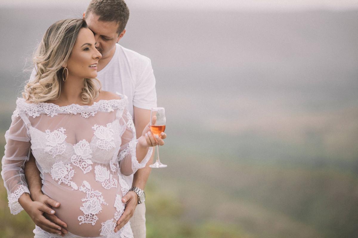 Gestante segurando uma taça de champagne abraçada com seu marido. Clicado pelo fotógrafo de gestantes Rafael Ohana em Brasília-DF