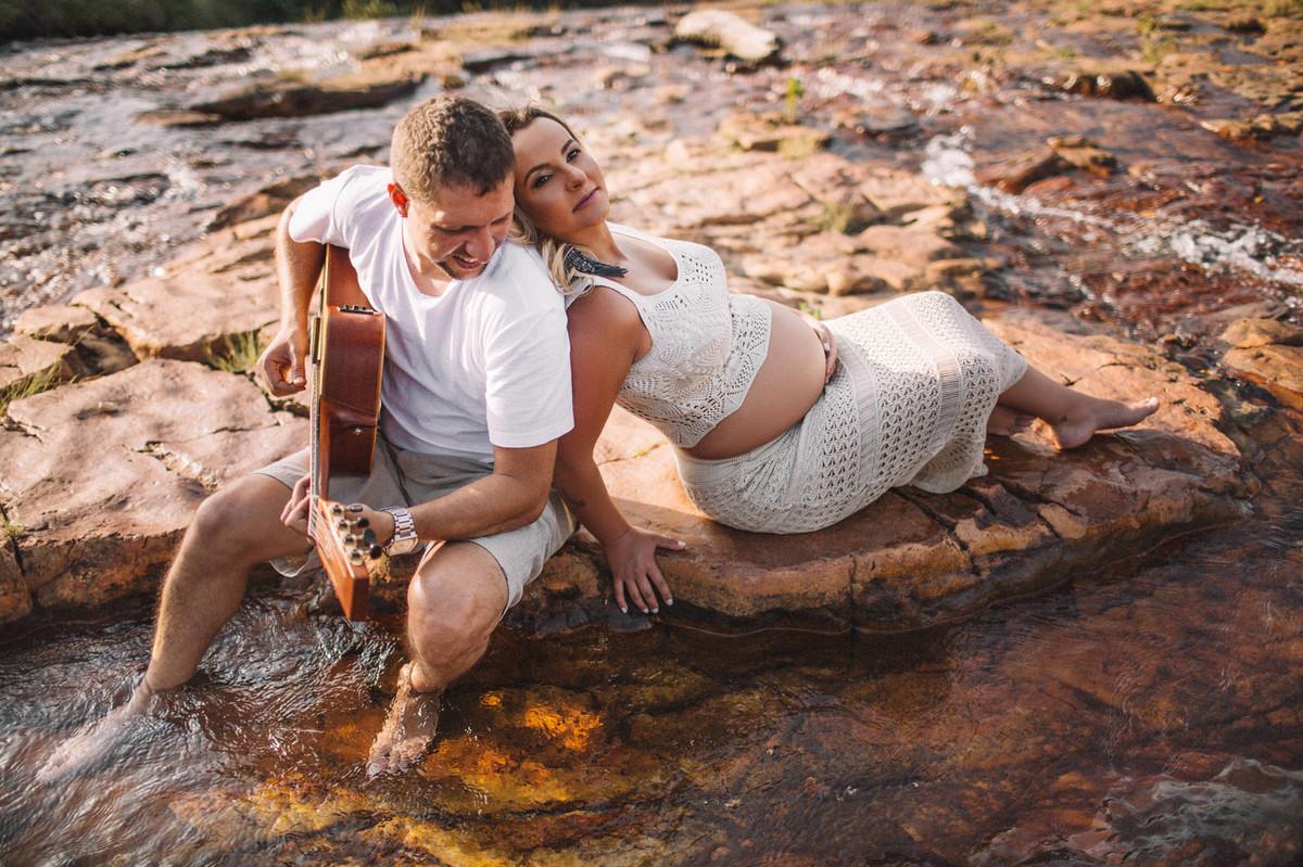 Esposo tocando violão para esposa grávida nas pedras de um rio. Clicado pelo fotógrafo de gestantes Rafael Ohana em Brasília-DF