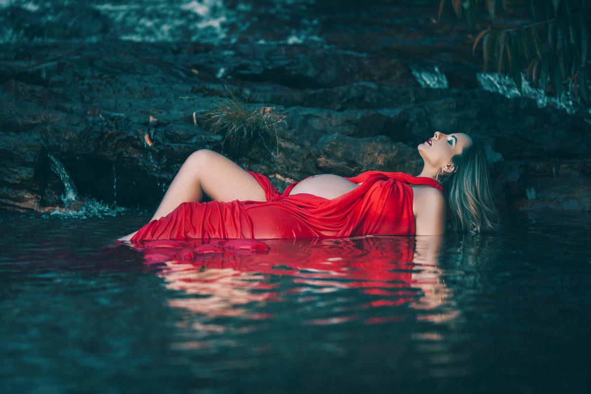 Gestante dentro da agua da cachoeira com vestido vermelho molhado. Clicado pelo fotógrafo de gestantes Rafael Ohana em Brasília-DF