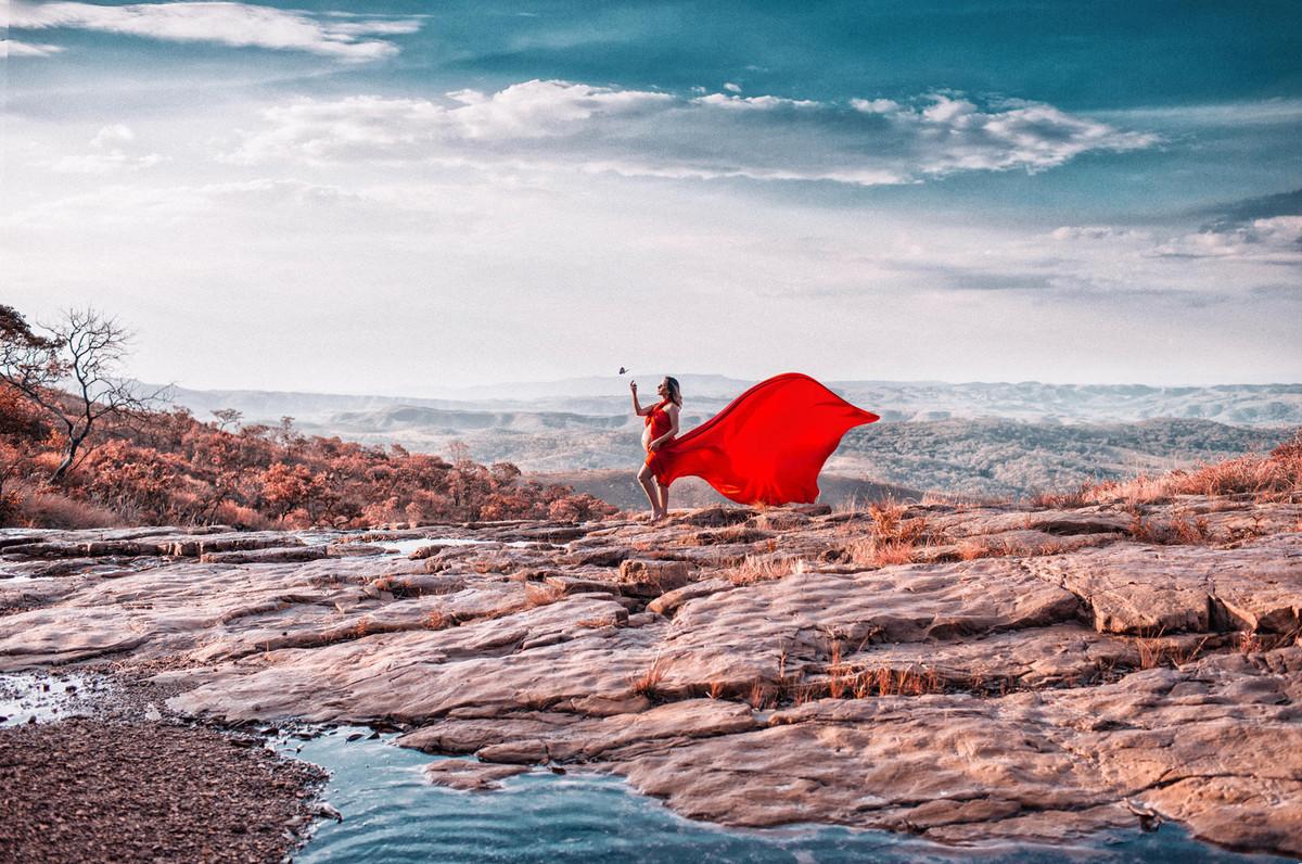 Grávida brindando com borboleta em pedras de rio. Clicado pelo fotógrafo de gestantes Rafael Ohana em Brasília-DF