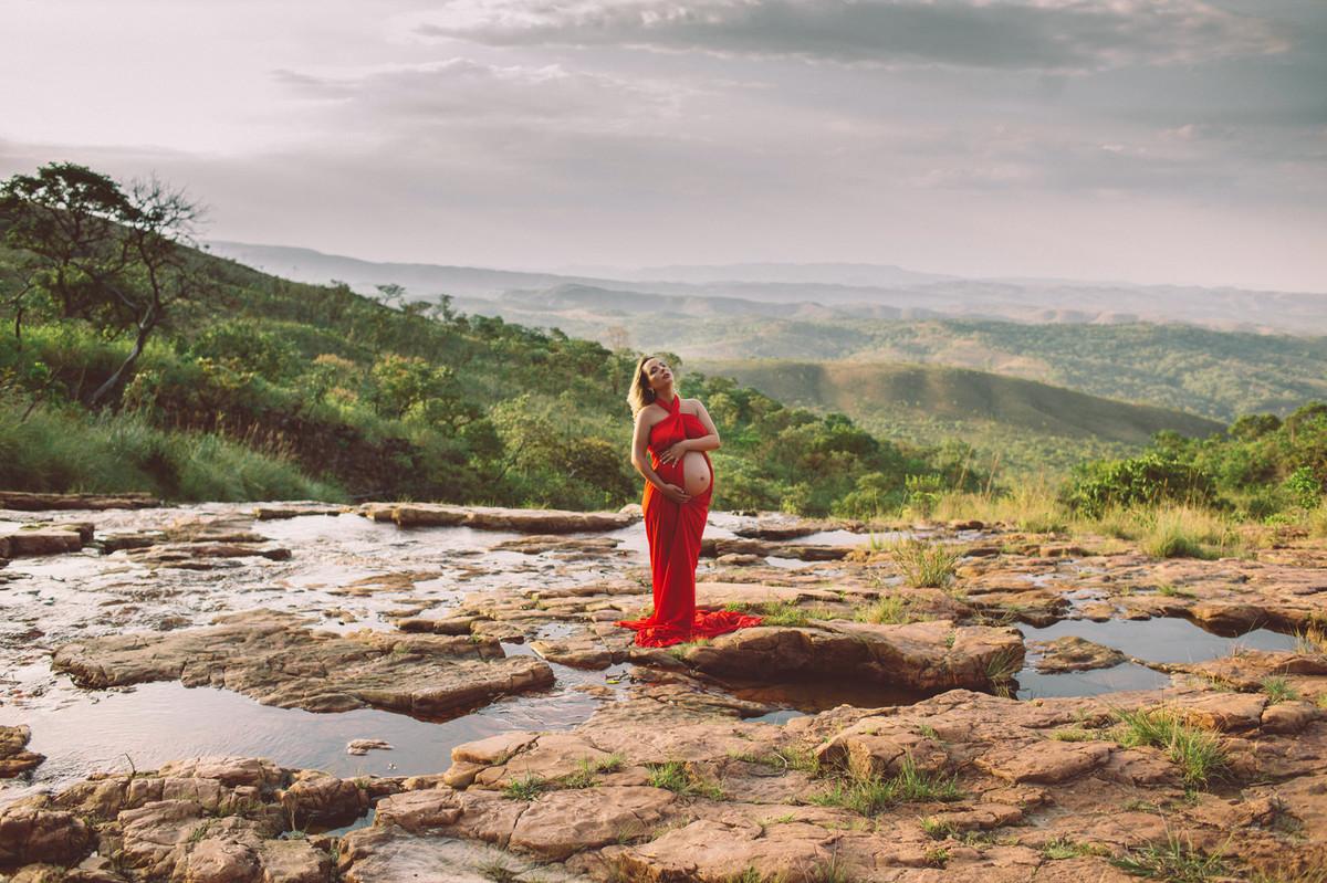 Grávida posando com seu vestido vermelho nas pedras do rio. Clicado pelo fotógrafo de gestantes Rafael Ohana em Brasília-DF