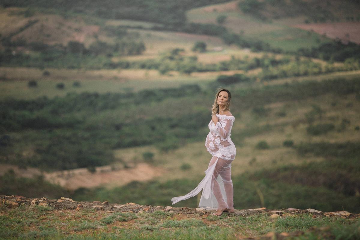Loira grávida usando vestido branco transparente perto de um precipício. Clicado pelo fotógrafo de gestantes Rafael Ohana em Brasília-DF