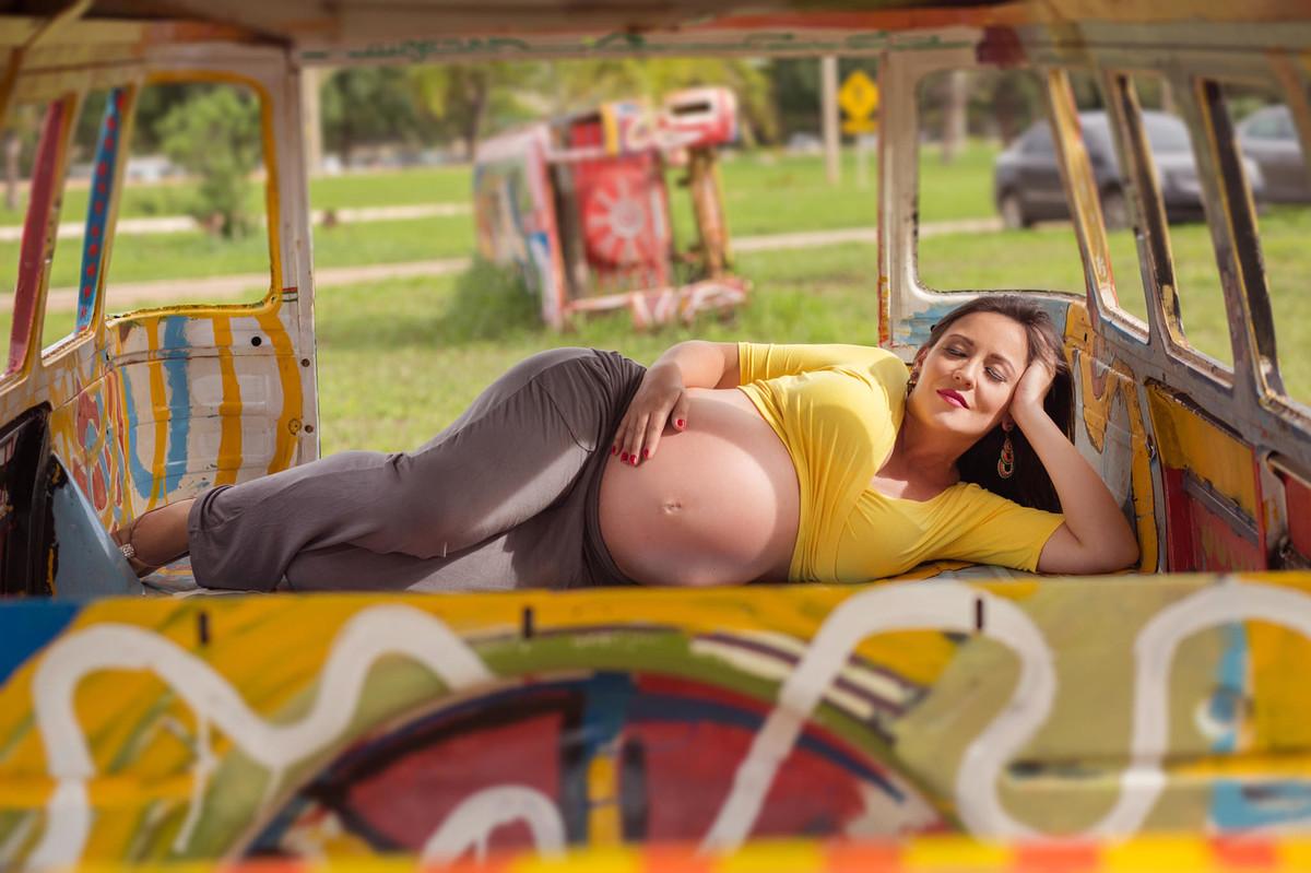 Grávida deitada dentro de carcaça de kombi. fotografia feita pelo fotógrafo de grávidas Rafael Ohana em Brasília