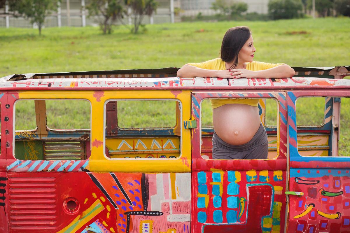 Grávida dentro de carcaça de kombi colorida. fotografia feita pelo fotógrafo de grávidas Rafael Ohana em Brasília