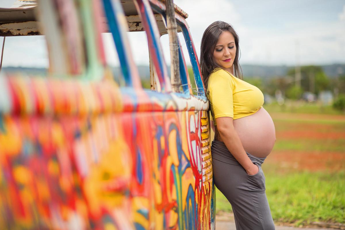 Gestante posando encostada na Kombi. fotografia feita pelo fotógrafo de grávidas Rafael Ohana em Brasília