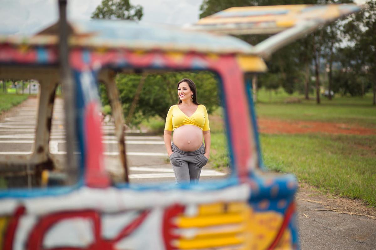 Gestante caminhando com as mãos nos bolsos. fotografia feita pelo fotógrafo de grávidas Rafael Ohana em Brasília
