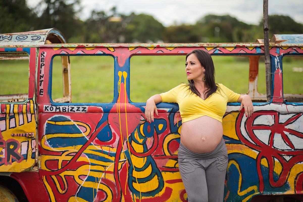 Grávida posando em kombi colorida. fotografia feita pelo fotógrafo de grávidas Rafael Ohana em Brasília