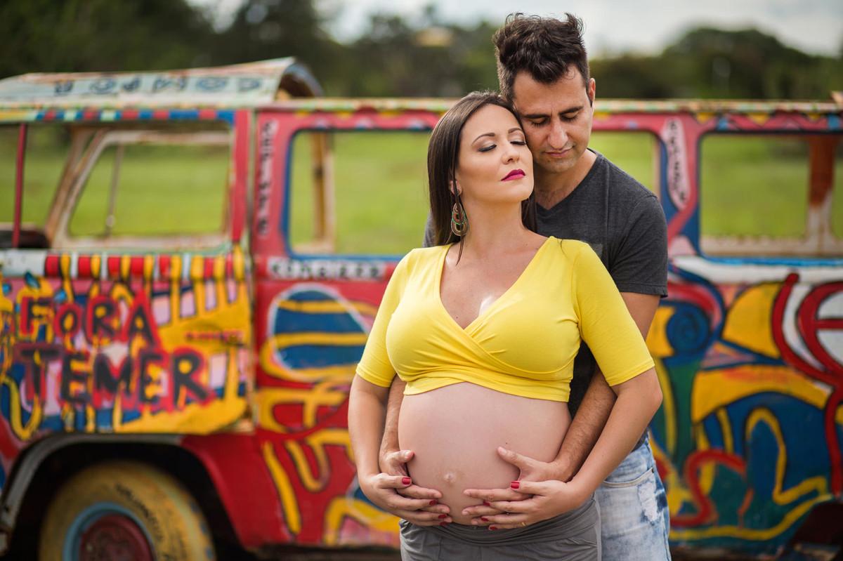 Marido abraçando grávida com kombi no fundo. fotografia feita pelo fotógrafo de grávidas Rafael Ohana em Brasília