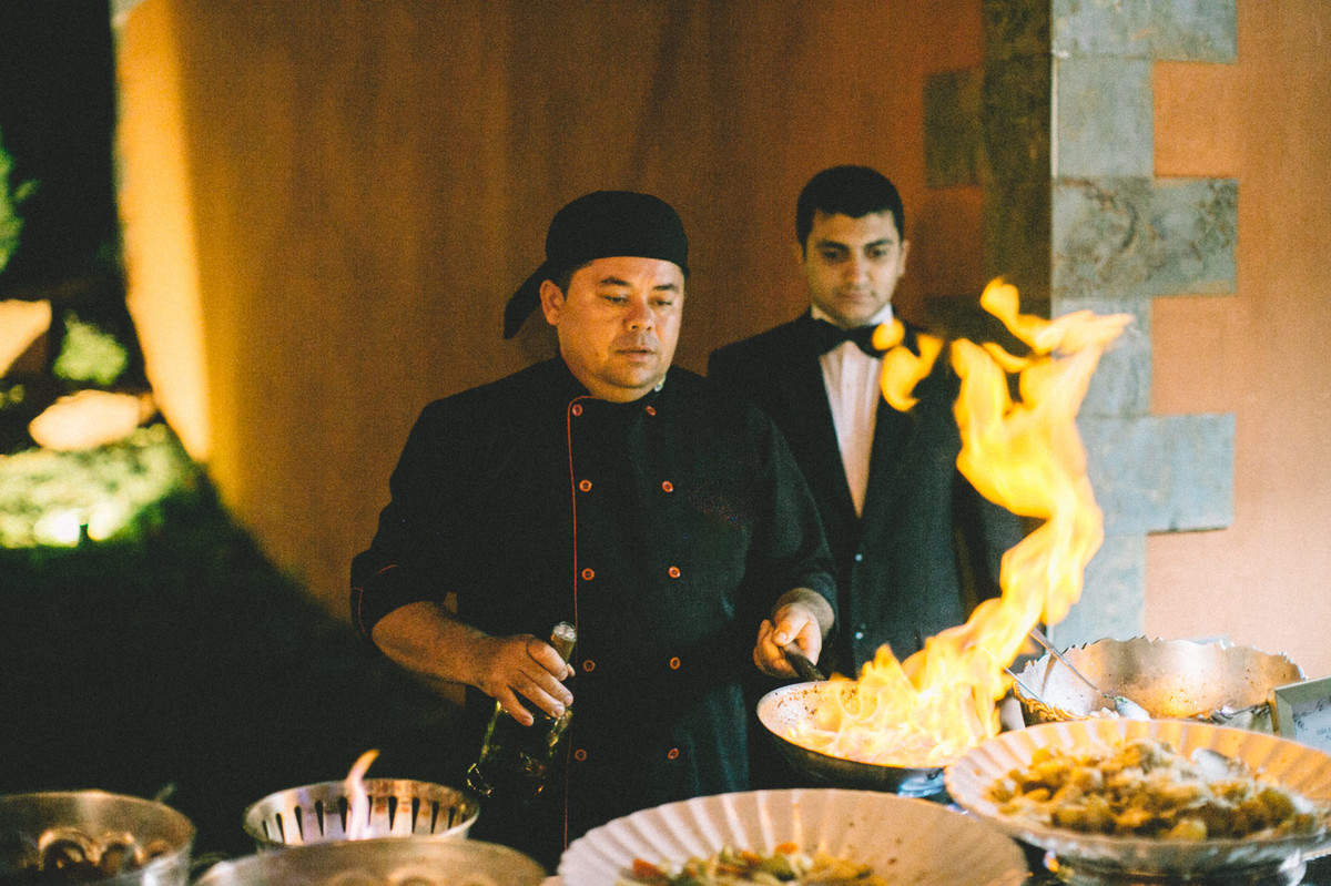 Chef de cozinha flambando camarões em recepção de casamento no Villa Giardini em Brasília-DF