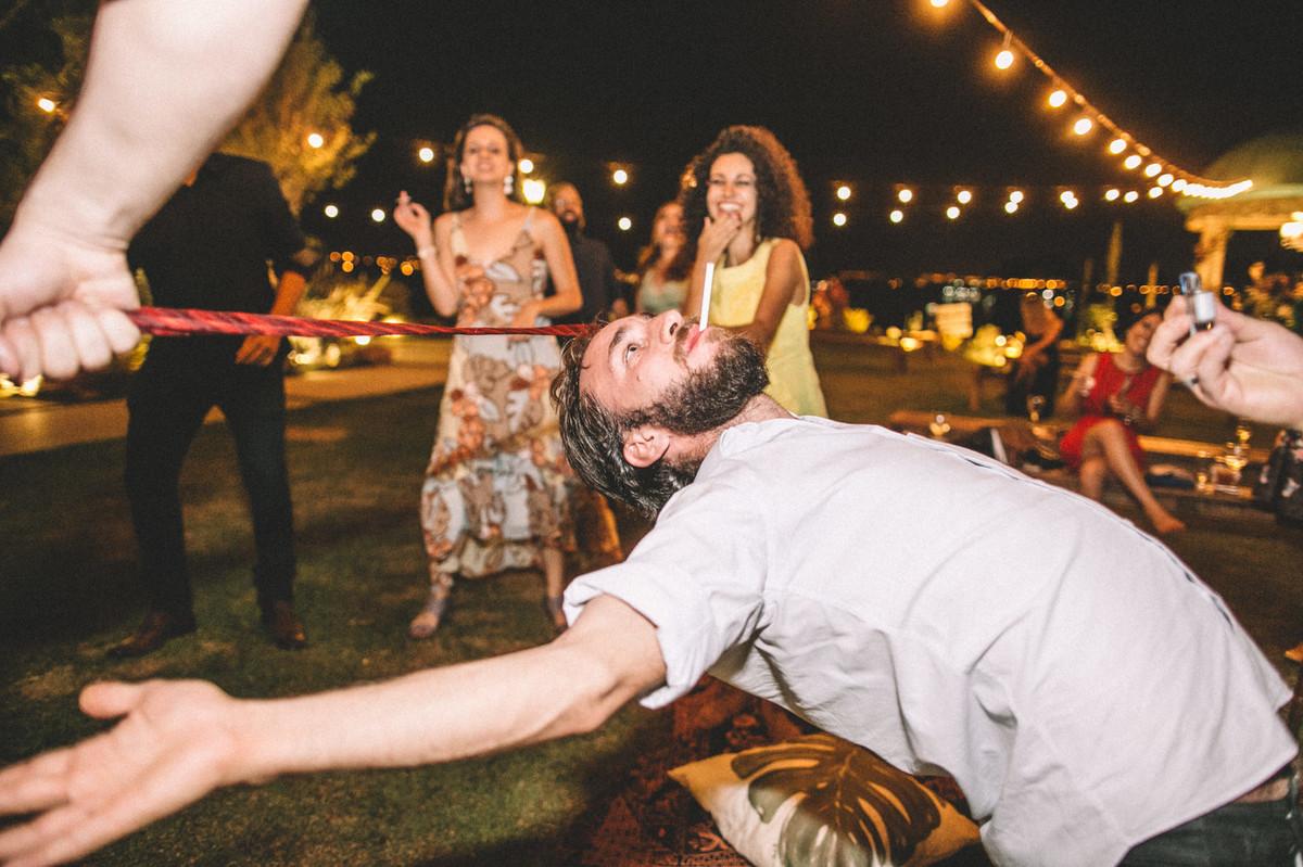 Convidado de casamento passando por debaixo da cordinha com cigarro na boca no Villa Giardini em Brasília-DF