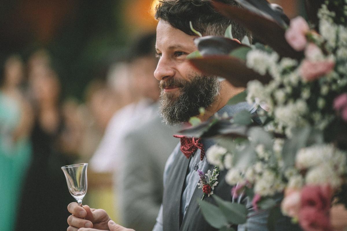 Convidado de casamento sorrindo com taça na mão no Villa Giardini em Brasília-DF