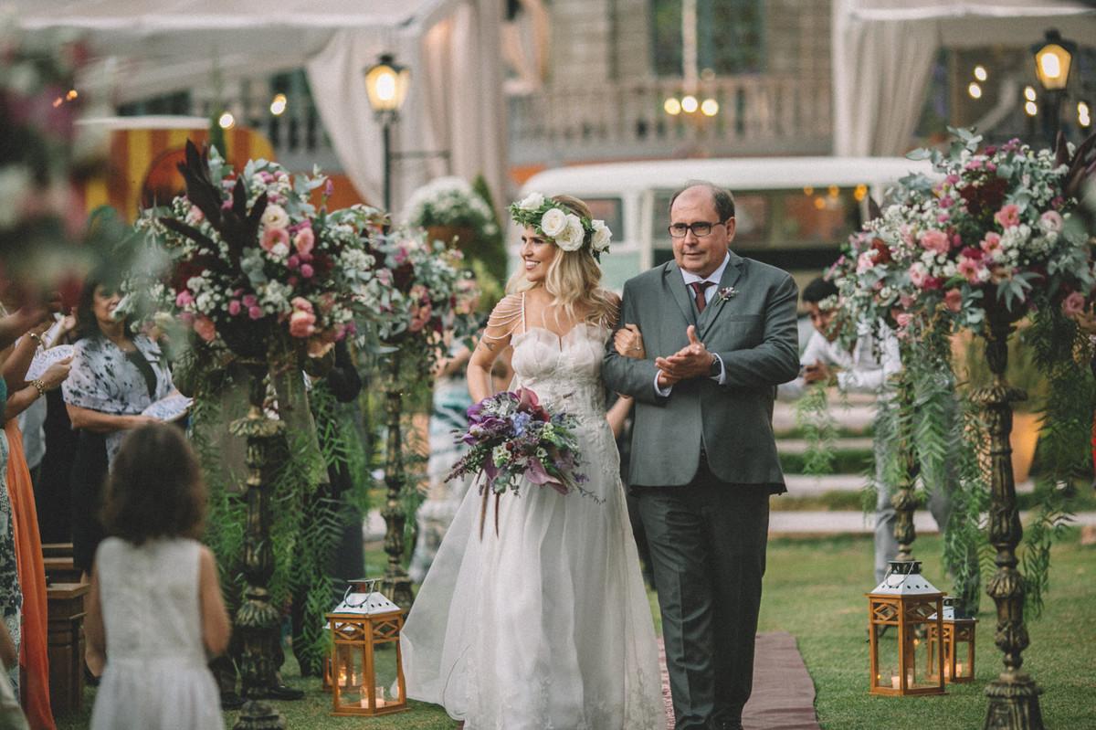 Noiva entrando em seu casamento sorrindo com seu pai no Villa Giardini em Brasília-DF