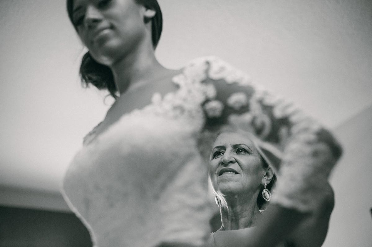 mae da noiva ajudando a filha a se vestir
