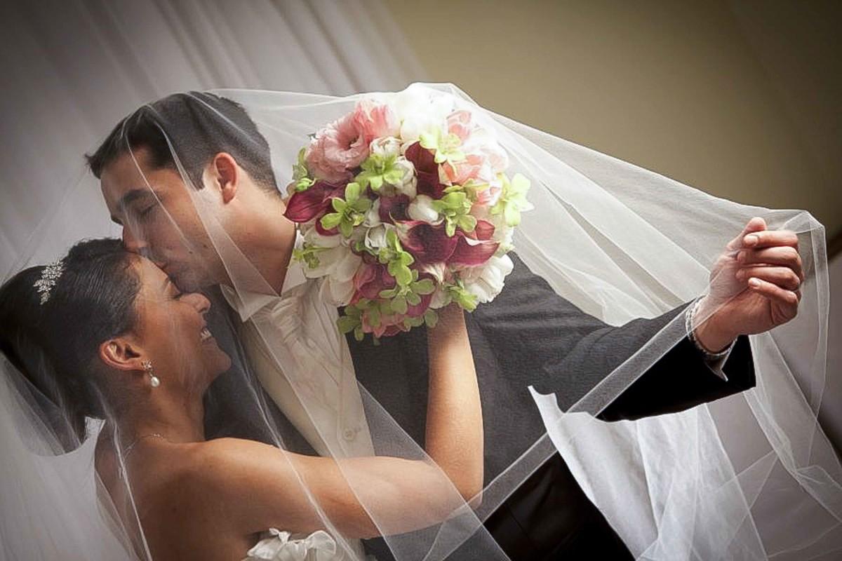 Os noivos apaixonados, beijam-se comemorando sua união, bouquet, flores, wedding destination